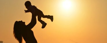 woman-carrying-baby-at-beach-during-sunset